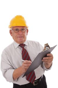 older worker wearing hard hat and writing on clipboard