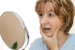middle aged woman looking into mirror